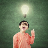 Intelligent child gets idea under bright light bulb Royalty Free Stock Images