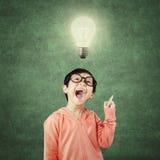 Intelligent child gets idea under bright light bulb Royalty Free Stock Photo