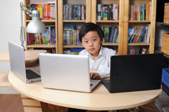 Intelligent child working on multiple computers Stock Photos