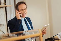 Intelligent clever man standing and using his gadgets. Business conversation. Intelligent clever occupied man standing in the room having phone conversation and Stock Photos