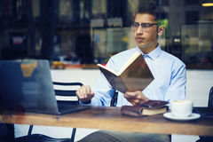 Intelligent concentrated male student searching information in internet. Sources and books for preparing for upcoming exam. Young man cafe interior and using Stock Images