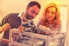 Intelligent coworkers trying to figure out the way to properly construct a 3D printer. Work of the future. Man and woman tinkering with the 3D printer in their royalty free stock images