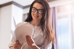 Intelligent delighted businesswoman looking through the documents Stock Image