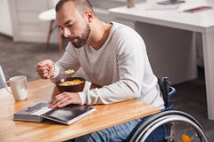 Intelligent disabled man looking through book in the morning Stock Photo