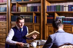 Intelligent elite and education concept. Young men with antique bookshelves. On background. Intelligent men, scientists spend leisure in library. Professors Stock Images