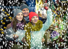 Intelligent family couple with teen daughter choosing Christmas. Decoration at fair Royalty Free Stock Photos