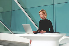 Intelligent female lawyer with cell telephone in hand keyboarding important document for lawsuit via net-book Stock Image