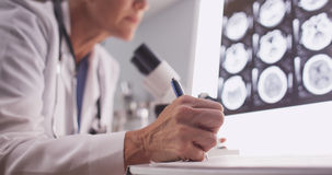 Intelligent female radiologist analyzing with microscope Royalty Free Stock Images