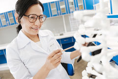 Intelligent female researcher studying genomics. Biological science. Intelligent positive female researcher standing in the lab and holding a tablet while Royalty Free Stock Image