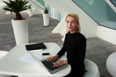 Intelligent female secretary posing in modern office interior during work on portable net-book. Young successful businesswoman looking at camera while sitting at Royalty Free Stock Photo