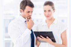 Intelligent gekleidete Kollegen, die digitale Tablette verwenden Stockbilder