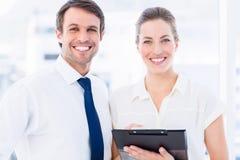 Intelligent gekleidete Kollegen, die digitale Tablette verwenden Lizenzfreie Stockfotos