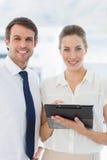 Intelligent gekleidete Kollegen, die digitale Tablette verwenden Stockfotos