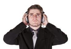 Intelligent gekleideter Mann, der auf Kopfhörern hört Stockbilder