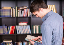 Intelligent Guy Reading a Book at the Library Royalty Free Stock Photos
