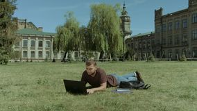 Smart male student working on laptop on campus lawn. Intelligent handsome male student working on laptop pc while lying down on campus green lawn. Smart stylish stock video