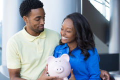 Intelligent investing. Closeup portrait, happy handsome couple or two business people holding pink piggy bank looking at each other, laughing.  Smart financial Royalty Free Stock Image