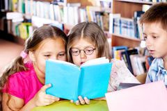 Intelligent kids. Reading a book Royalty Free Stock Images
