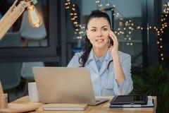 Intelligent kvinnlig doktor som diskuterar arbete på telefonen arkivfoto