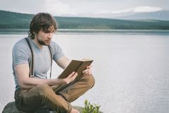 Intelligent man reading book outdoor lake and mountains landscape royalty free stock photography