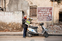 Intelligent man reading the latest news in a newspaper, standing on dirty street of town Royalty Free Stock Photos