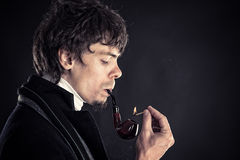 Intelligent man smokes tobacco. On black background Royalty Free Stock Images