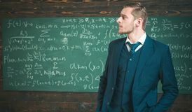 Intelligent man in suit at elite university. Side view blond guy with stylish hairstyle, beard and mustache royalty free stock images
