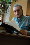 Intelligent mannelijk de lezingsboek en zitting van de hipsterstudent bij de lijst in openbare universitaire bibliotheek Zijaanzi Royalty-vrije Stock Afbeeldingen