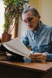 Intelligent mannelijk de lezingsboek en zitting van de hipsterstudent bij de lijst in openbare universitaire bibliotheek Zijaanzi Stock Foto's