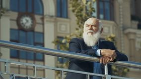 Intelligent old man near the building. Slowmotion. Old gray-haired man wearing suit is outdoors. Intelligent elderly man stands near the railing in front of the stock video footage