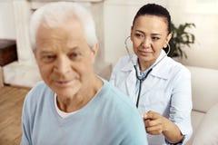 Intelligent positive nurse doing medical checkup Royalty Free Stock Images