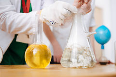 Intelligent professional scientist putting something to a flask. See what is happening. Intelligent professional scientist standing at the table and putting Royalty Free Stock Image