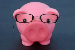 Intelligent Savings. A pink piggy bank with a pair of specs (glasses) isolated on black background Stock Image
