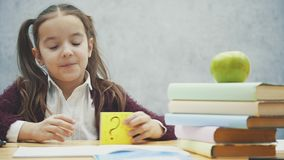 Intelligent schoolgirl, sitting at the table. During this time a sticker on a yellow sheet is kept. Has a sad view.