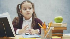 Intelligent skolflicka p? en gr? bakgrund Under denna tid sitter han p? tabellen Skriver f?rsiktigt l?xa lager videofilmer