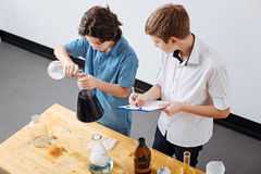 Intelligent smart boys working on a scientific project. Science lesson. Intelligent smart serious boys standing in the classroom and conducting an experiment Royalty Free Stock Image