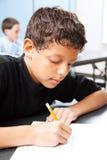 Intelligent Student Takes Test. Intelligent school boy taking a standardized test in school Stock Photography