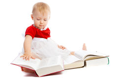 Intelligent toddler. An intelligent toddler reading thick books, isolated Stock Photo