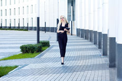 Intelligent woman with notebook walks down the street against the background of the business center Stock Images