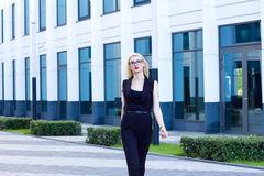 Intelligent woman walks down the street against the background of the business center Stock Photos