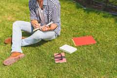 Intelligent young man making notes in park Royalty Free Stock Photography