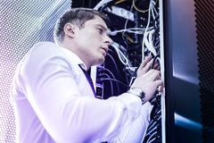 Intelligent young man standing near the box with wires stock image