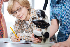 Intelligent young students working on biology project royalty free stock photo