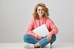 Intelligent young woman with curly hair sitting on floor with crossed legs, wearing trendy eyewear and hoodie, holding. Closed laptop and smiling at camera Royalty Free Stock Images