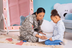 Intelligent young woman explaining math to her daughter. Simple as that. Confident caring wonderful mother charting a table using a pencil trying helping her stock image