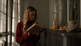 Intelligent young woman reading a book at home stock footage