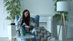 Pretty woman reading a book in armchair at home stock video