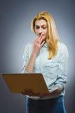 Intelligente attraktive Frau, die auf Laptop schaut Lizenzfreie Stockbilder