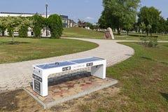 Intelligente Bank im Stadtpark einer modernen Stadt von Tiszaujvaros in Ungarn stockfotografie