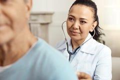 Intelligente begeisterte Krankenschwester, die um ihren Patienten sich kümmert Lizenzfreie Stockfotos